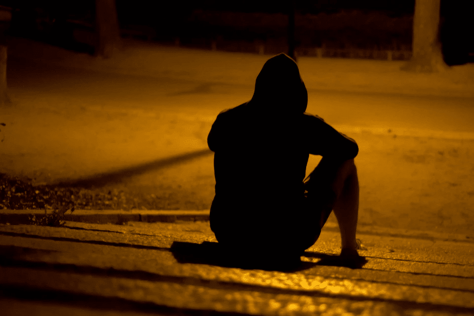 Lonely Man Sitting in a Dark Park