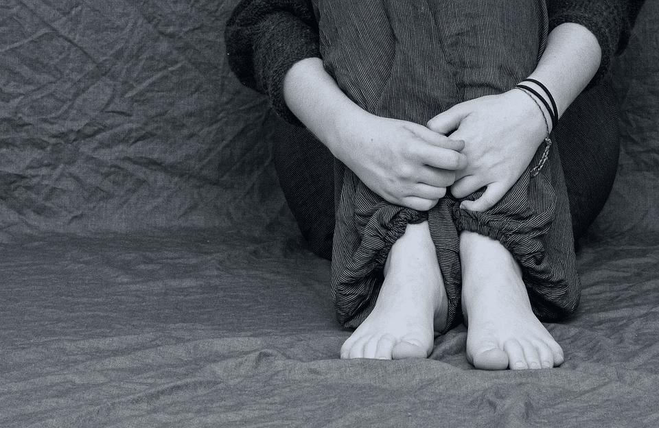 Feet and hands of a depressed girl