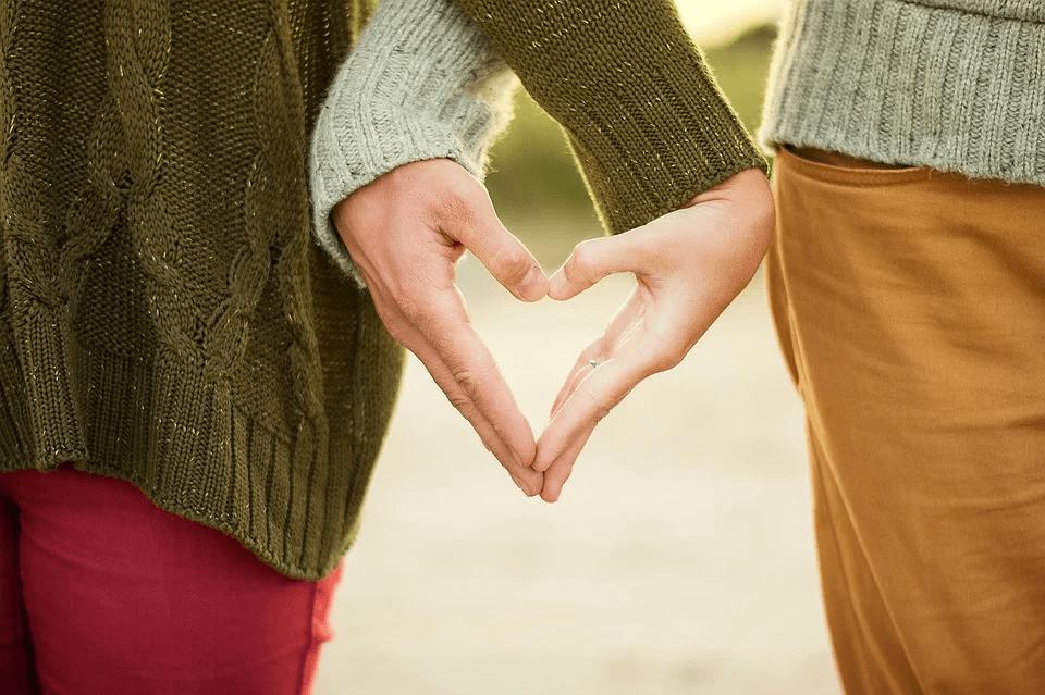 Pasangan muda membentuk hati dengan tangan mereka