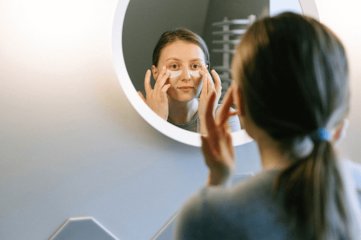 woman looking at herself in the mirror adding under eye patches