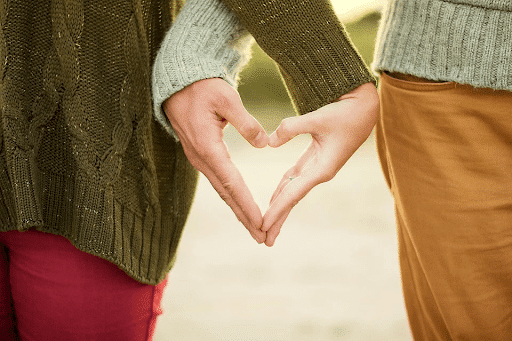 Young couple forming a heart with their hands