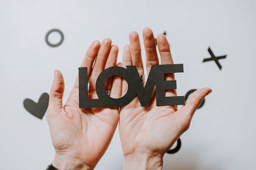 Person holding love word cutout
