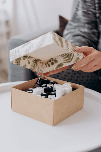 beauty products inside a box with a female hand opening the top lid of the box (cosmetics distribution image)