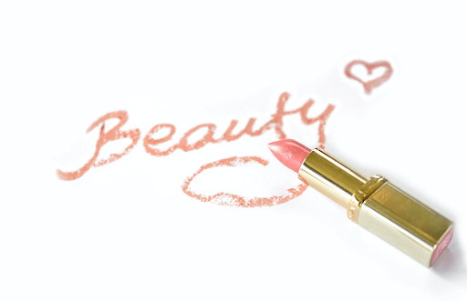 the word beauty written in pink with a pink lipstick