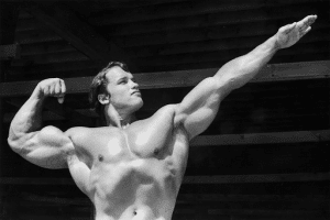 black and white photo of Arnold Schwarzenegger as Mr. Olympia flexing his muscles