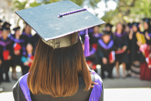woman with her back turned wearing an academic cap while looking at her classmates who are blurry in the background
