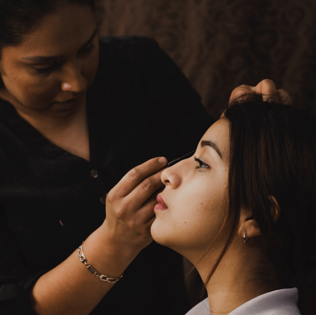woman applying makeup to another woman (mobile beauty business image)