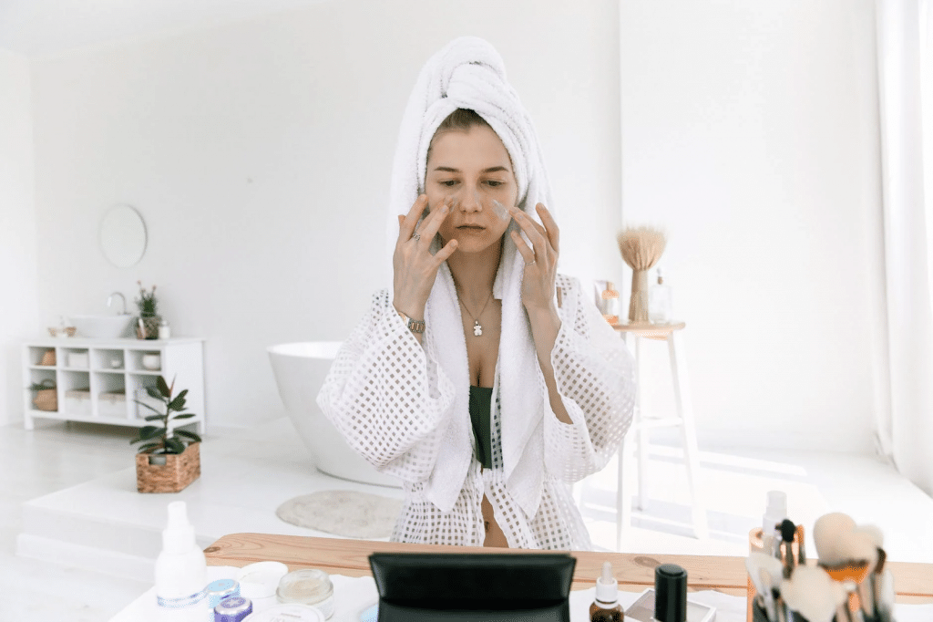woman applying skincare with makeup and skincare products surrounding her