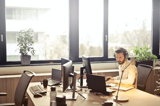 Man with headphones facing a computer monitor