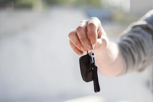 Person in a grey shirt handing car keys