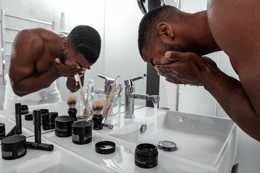 man washing his face in front of a mirror with running tap water, and skincare products in the sink