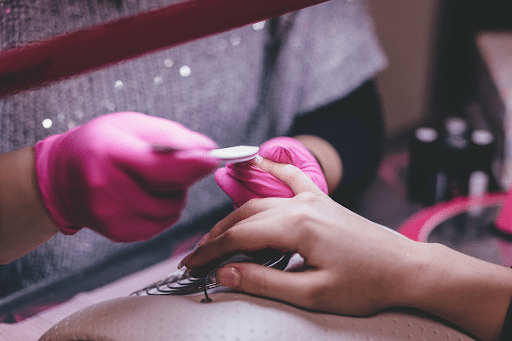 pink gloves giving a manicure to a lady's hand