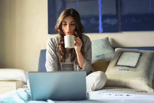 A woman in her bed blowing a coffee mug and seated in front of a grey laptop
