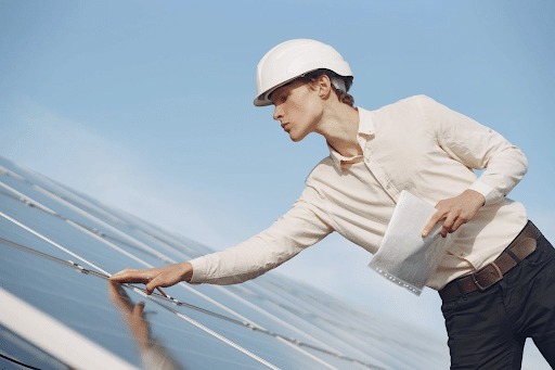 A man in a white long-sleeve top touching solar panels while working on a project