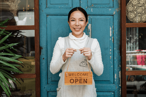 """A female cafe owner showing a """"Welcome we are open"""" inscription"""