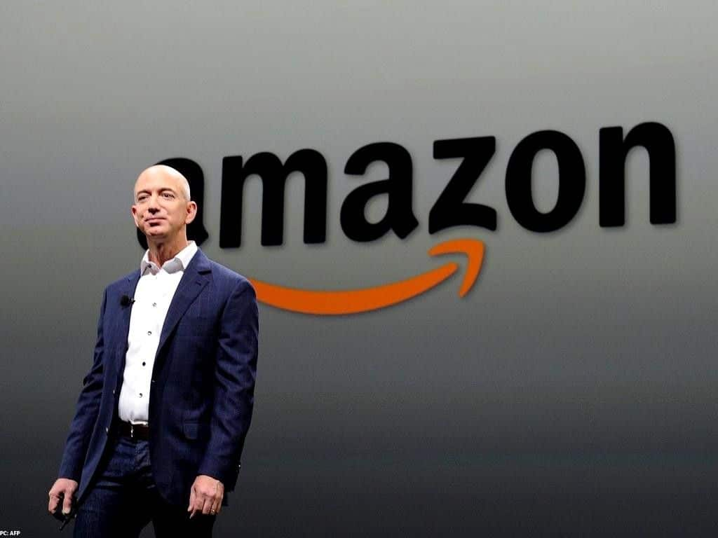 Standing Jeff Bezos on a blue suit with Amazon's logo behind him