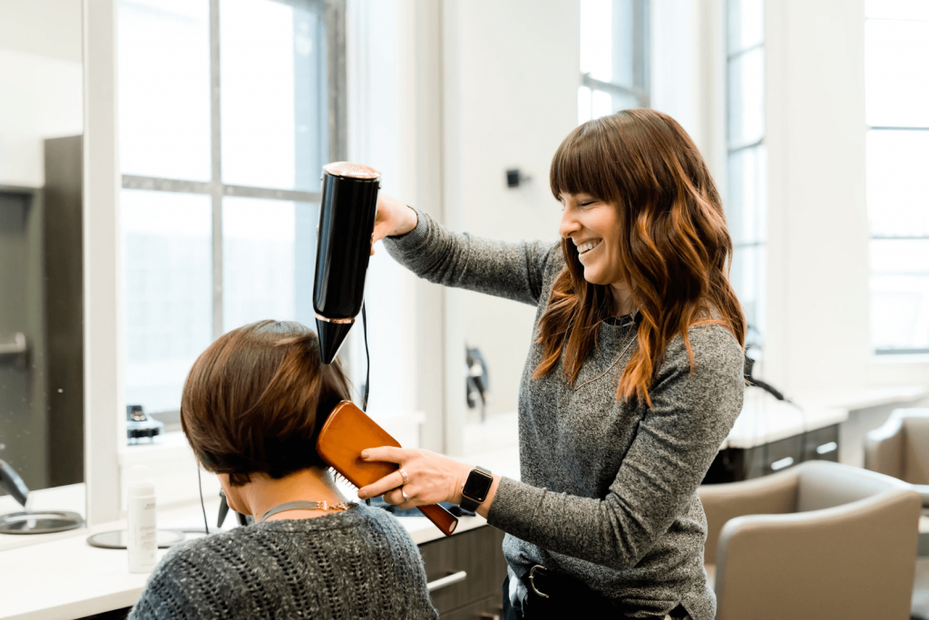 smiling woman holding a hairdryer over another woman's hair, with her other hand holding a brush