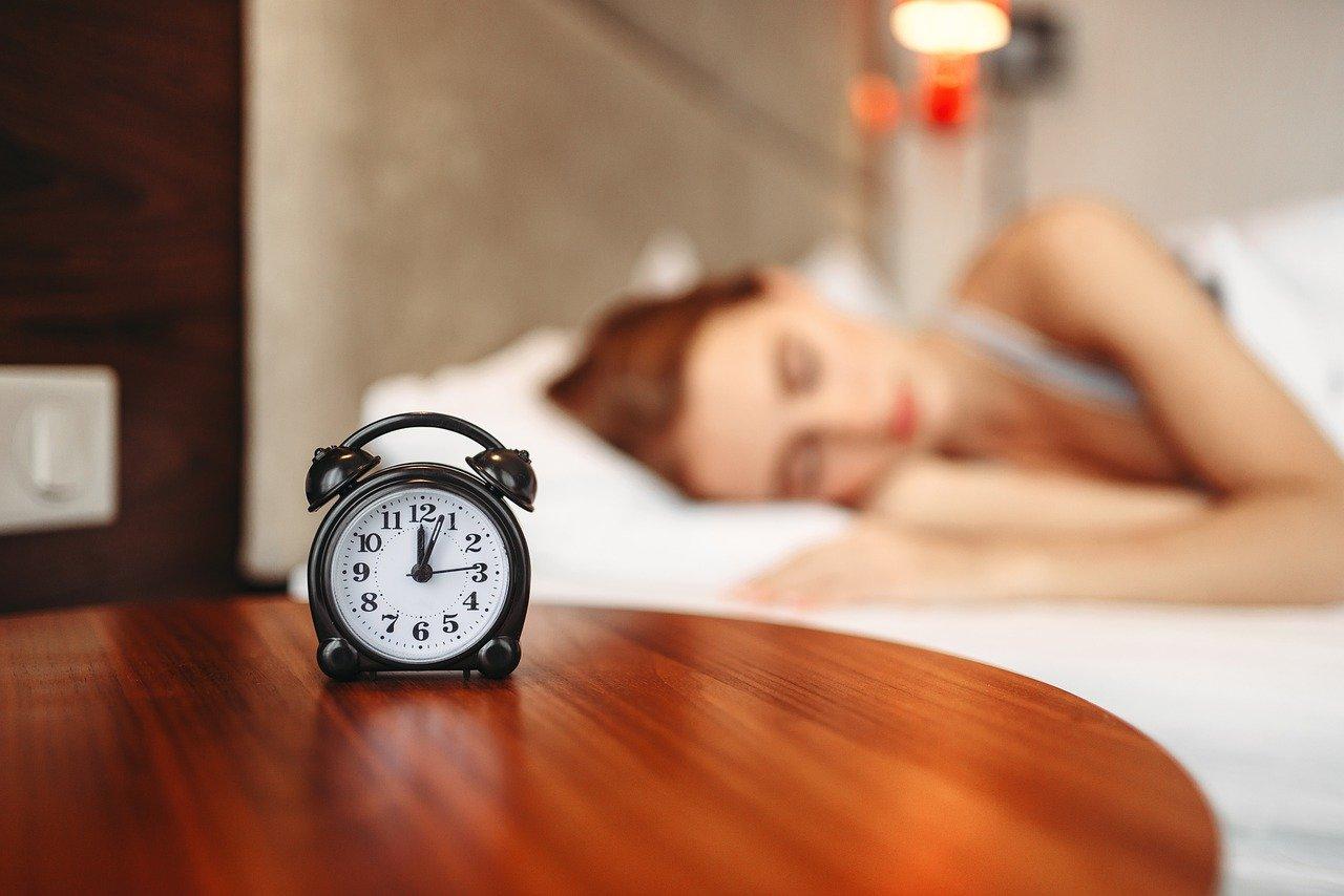 A black alarm clock on a wooden table beside a sleeping woman