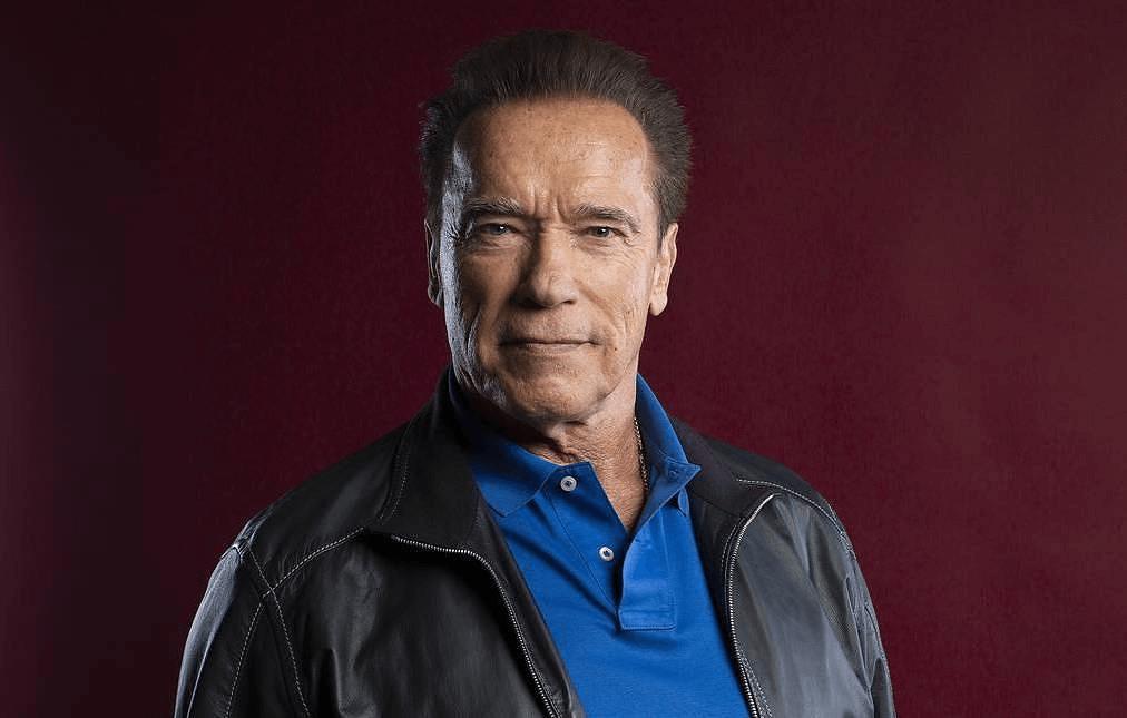 Arnold Schwarzenegger smiling in front of a black background