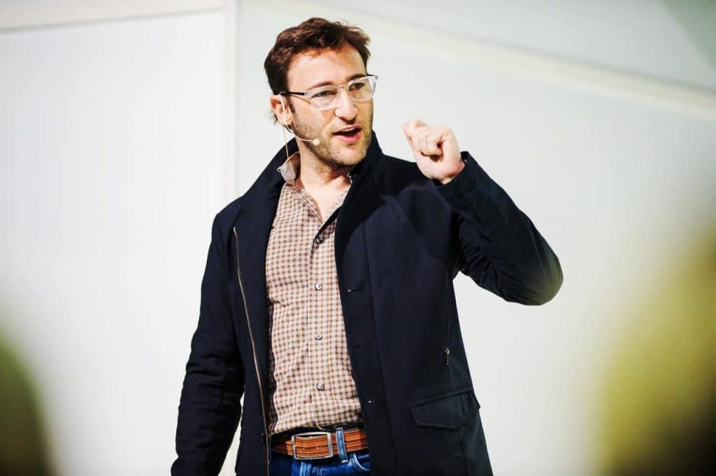 Simon Sinek in a black coat with a pleated top speaking for nbforum