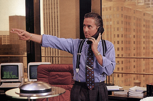 Gordon Gekko on a blue long-sleeve polo talking to someone on the phone while pointing to his left side