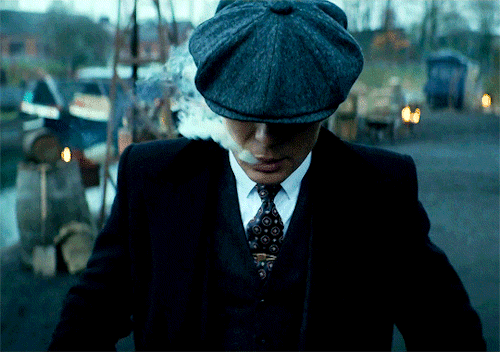 Thomas Shelby exhaling cigarette smoke while walking forward with his eyes covered by his hat
