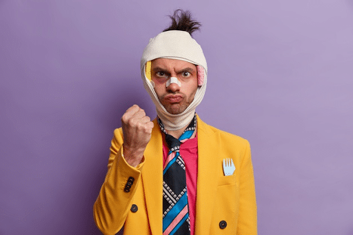 half body shot of injured man wearing a yellow suit and a colorful tie