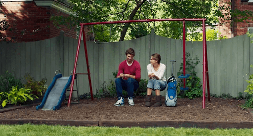 Gus and Hazel talking while sitting on a kid's swing