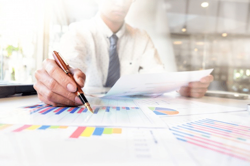 A businessman in a while polo holding a pen over a printed bar graph on the table