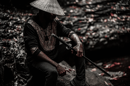 Man in black top and jeans and white sun hat holding a samurai sword