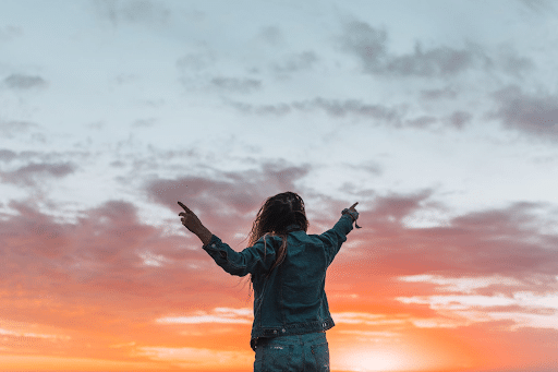 Faceless woman pointing with fingers at the bright sky in twilight