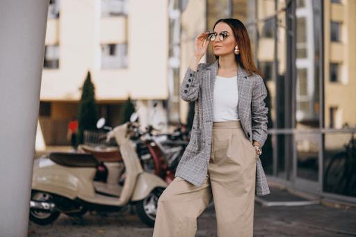 stylish classy woman wearing a gray checkered suit, khakis, and sunglasses