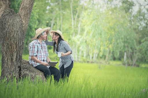 A woman holding a cup and an old man seated near a tree trunk on a grassy countryside