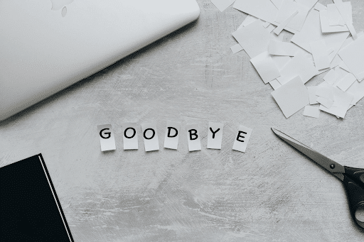Cut GOODBYE letters, scissors, laptop, and pieces of paper on a grey table