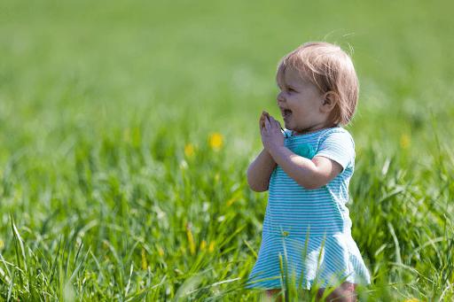 A baby girl wearing a green dress on a green grass field