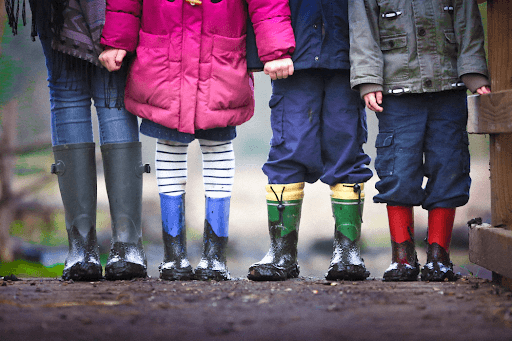 Lower bodies of four kids wearing muddy boots