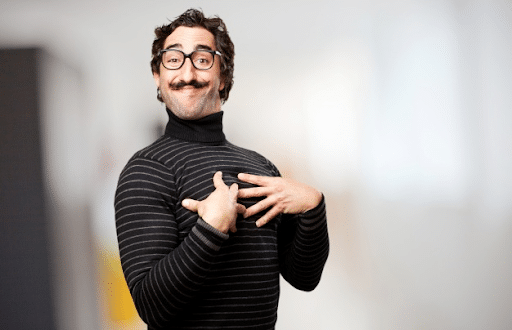 A bearded man with glasses wearing a black turtleneck long sleeve blouse posing his hands on his chest