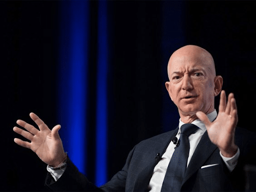 Frowning Jeff Bezos with both of his hands spread out