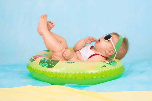 A baby wearing sunglasses lying on a green inflatable ring on a blue background
