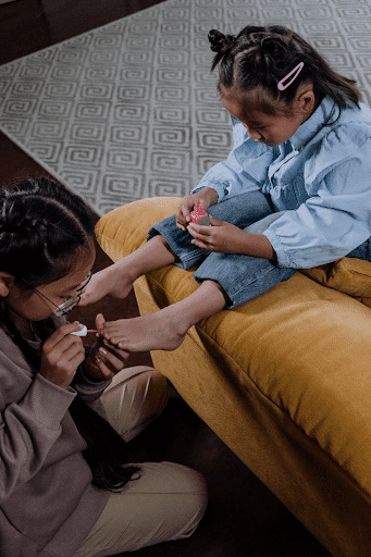 girl sitting on a brown sofa having her foot pedicured by her sister (crazy sister image)