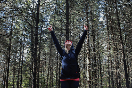 A woman in a forest wearing a dark blue hoodie raising her hands up