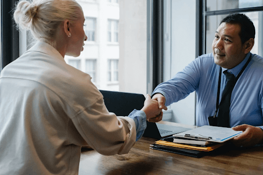 A businessman shaking an applicant's hand inside his office