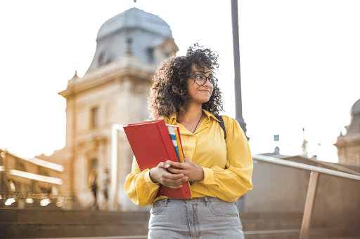 A curly-haired female student in a yellow long-sleeve polo shirt holding books