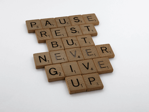 """brown wooden blocks spelling out """"pause rest but never give up"""""""
