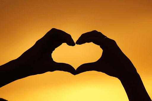 Silhouette of a person's hand forming a heart