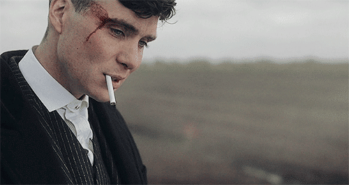 Thomas Shelby shaking his bleeding head while holding an unlit cigarette in his mouth