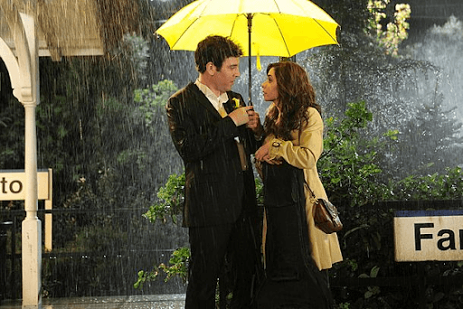 Ted and Tracy under a yellow umbrella in a rainy scene