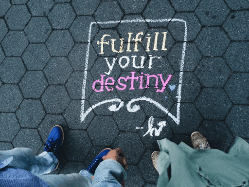 """Two people standing near a """"fulfill your destiny"""" street artwork"""