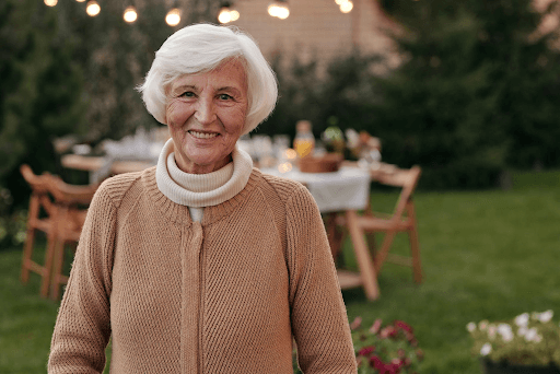 Cheerful smiling old woman in a backyard