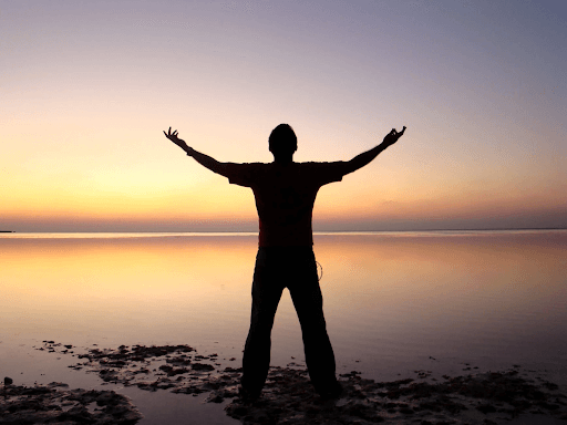 Silhouette of a man extending his arms up while standing beside an ocean during sunset
